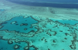 """TO GO WITH AFP STORY BY LAURENCE COUSTAL (FILES) This file photo taken on November 20, 2014 shows an aerial view of the Great Barrier Reef off the coast of the Whitsunday Islands, along the central coast of Queensland. Coral reefs, that the Tara Pacific expedition go study on May 28, 2016 in the Pacific, are """"half animal half plant and risk a lot with climate change. Sarah Lai / AFP"""