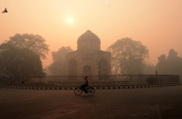 "An Indian cyclist rides along a street as smog envelops a monument in New Delhi on October 31, 2016, the day after the Diwali festival. New Delhi was shrouded in a thick blanket of toxic smog a day after millions of Indians lit firecrackers to mark the Diwali festival, causing the air pollution to hit ""severe"" level. The pollutants breached the 1000 microgram mark in the Indian capital and shot up nearly 10 times above the normal level in  the early hours of Monday, mostly owing to bursting of millions of firecrackers, according to a weather scientist.  / AFP PHOTO / MONEY SHARMA"