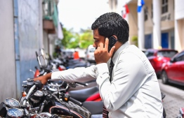 A man speaks on the phone. PHOTO: HUSSAIN WAHEED / MIHAARU