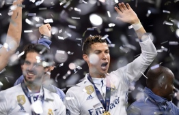 Real Madrid's Portuguese striker Cristiano Ronaldo (R) raises a hand after Real Madrid won the UEFA Champions League final football match between Juventus and Real Madrid at The Principality Stadium in Cardiff, south Wales, on June 3, 2017. / AFP PHOTO / Filippo MONTEFORTE