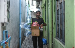 State-owned Waste Management Corporation Limited (WAMCO)'s staff taking out garbage from a home in capital Male City. PHOTO: HUSSAIN WAHEED/MIHAARU