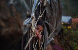 A Rohingya girl looks out from a makeshift shelters at Hakimpara refugee camp in the Bangladeshi district of Ukhia on November 13, 2017.   More than 600,000 Rohingya have arrived in Bangladesh since a military crackdown in Myanmar in August triggered an exodus, straining resources in the impoverished country. / AFP PHOTO / Munir UZ ZAMAN