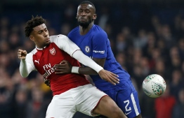 Arsenal's Nigerian striker Alex Iwobi (L) vies with Chelsea's German defender Antonio Rudiger during the English League Cup semi-final first leg football match between Chelsea and Arsenal at Stamford Bridge in London on January 10, 2018. / AFP PHOTO / Ian KINGTON / RESTRICTED TO EDITORIAL USE. No use with unauthorized audio, video, data, fixture lists, club/league logos or 'live' services. Online in-match use limited to 75 images, no video emulation. No use in betting, games or single club/league/player publications.  /