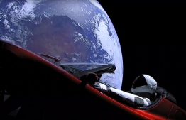 "This still image taken from a SpaceX livestream video shows ""Starman"" sitting in SpaceX CEO Elon Musk's cherry red Tesla roadster after the Falcon Heavy rocket delivered it into orbit around the Earth on February 6, 2018. Screams and cheers erupted at Cape Canaveral, Florida as the massive rocket fired its 27 engines and rumbled into the blue sky over the same NASA launchpad that served as a base for the US missions to Moon four decades ago. / AFP PHOTO / SPACEX / HO /"