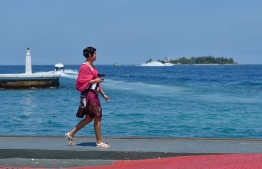 A tourist pictured walking along the wharf of Male. PHOTO: HUSSAIN WAHEED/MIHAARU