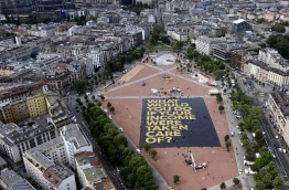 "A giant poster reading: ""What would you do if your income was taken care of?"" is laid out on May 14, 2016 in Plainpalais place in Geneva (AFP Photo/Fabrice Coffrini)"