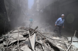 Syrians walk through the rubble following a reported air strike by Syrian government forces in the rebel-held neighbourhood of Bustan al-Qasr on June 5, 2016. / AFP PHOTO / Baraa Al-Halabi
