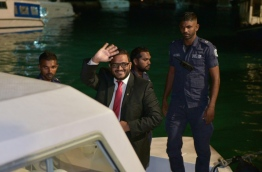 Former VP Adheeb waves as he is escorted to prison after being sentenced to 10 years for weapon possession. MIHAARU PHOTO/MOHAMED SHARUHAAN
