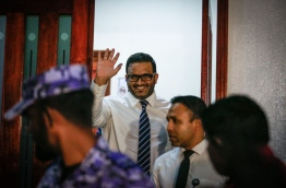 Former VP Adheeb waves to reporters after he exits the Criminal Court following the verdict. MIHAARU PHOTO