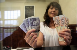 Delia Breen, who works in a money exchange office at the border between Newry in Northern ireland and Dundalk in The Republic of Ireland poses with handfuls of Sterling notes and Euro notes, on June 7, 2016. AFP PHOTO