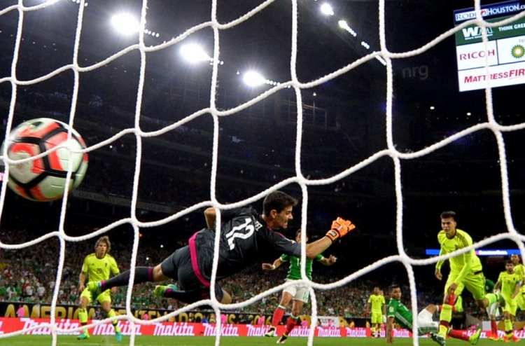 bf6ad6fc0 ... Mexico s Jesus Manuel Corona (R in green jersey) scores against  Venezuela during their Copa