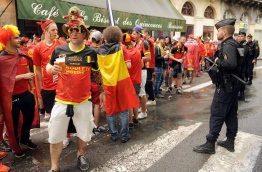 Police officers stand guard by Belgium supporters wearing Belgian football jersey and Belgium's national flag as they gather in the streets of Bordeaux, on June 18, 2016 ahead of the Euro 2016 group E football match between Belgium and Ireland at the Matmut Atlantique stadium in Bordeaux. / AFP PHOTO / IROZ GAIZKA
