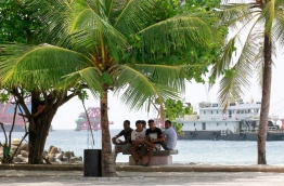 Some expats take shelter under a palm tree on a hot day in the capital Male. Government is looking to impose a tax on remittances to raise revenue. MIHAARU PHOTO/MOHAMED SHARUHAAN