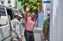 Former defence minister Nazim waves as he is escorted into the Supreme Court on Tuesday. MIHAARU PHOTO/NISHAN ALI