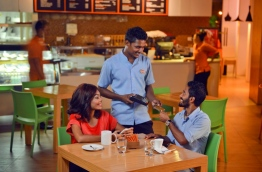 A BML customer uses a credit card at a local cafe. PHOTO/BML