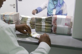 A man counts a stack of notes at a MMA counter. MIHAARU FILE PHOTO/MOHAMED SHARUHAAN