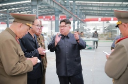 This undated picture released from North Korea's official Korean Central News Agency (KCNA) on July 27, 2016 shows North Korean leader Kim Jong-Un (C) inspecting the Chollima building materials complex in Pyongyang. / AFP PHOTO / KCNA / KCNA / South Korea
