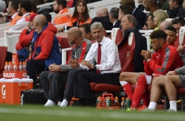 Arsenal's French manager Arsene Wenger (C) sits in the team dugout during the English Premier League football match between Arsenal and Chelsea at the Emirates Stadium in London on September 24, 2016. / AFP PHOTO / Ben STANSALL
