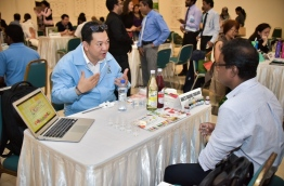 A representative of a Thailand export firm gives information on his company products to a Maldivian businessman at the forum held in Dharubaaruge. PHOTO: NISHAN ALI/MIHAARU