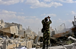 """A Syrian soldier inspects the wreckage of a building described as part of the Scientific Studies and Research Centre (SSRC) compound in the Barzeh district, north of Damascus, during a press tour organised by the Syrian information ministry, on April 14, 2018. The United States, Britain and France launched strikes against Syrian President Bashar al-Assad's regime early on April 14 in response to an alleged chemical weapons attack after mulling military action for nearly a week. Syrian state news agency SANA reported several missiles hit a research centre in Barzeh, north of Damascus, """"destroying a building that included scientific labs and a training centre"""". / AFP PHOTO / LOUAI BESHARA"""
