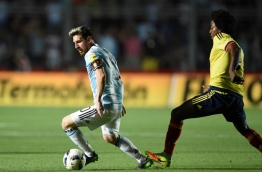 Argentina's Lionel Messi (L) is marked by Colombia's Carlos Sanchez during their 2018 FIFA World Cup qualifier football match in San Juan, Argentina, on November 15, 2016. / AFP PHOTO / EITAN ABRAMOVICH
