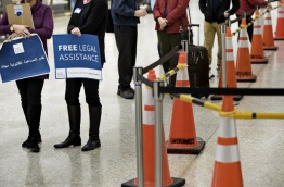 Volunteers wait to offer free legal advice to travelers at the international arrivals hall at Washington Dulles International Airport February 6, 2017 in Dulles, Virginia. / AFP PHOTO / Brendan Smialowski