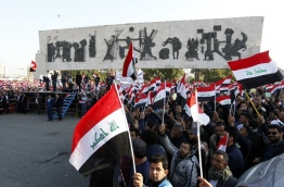 Iraqi supporters of the Sadrist movement hold national flags during a demonstration in Baghdad's Tahrir Square on February 11, 2017, to demand the formation of an independent electoral commission. / AFP PHOTO / SABAH ARAR