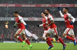 Arsenal's Chilean striker Alexis Sanchez (L) celebrates with teammates after scoring the opening goal of the English Premier League football match between Arsenal and Hull City at the Emirates Stadium in London on February 11, 2017. / AFP PHOTO / Glyn KIRK / RESTRICTED TO EDITORIAL USE. No use with unauthorized audio, video, data, fixture lists, club/league logos or 'live' services. Online in-match use limited to 75 images, no video emulation. No use in betting, games or single club/league/player publications. /