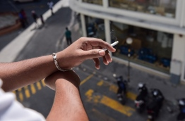 A person pictured holding a lit cigarette. MIHAARU FILE PHOTO