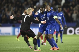 Leicester City's Nigerian midfielder Wilfred Ndidi (C), Leicester City's English-born Jamaican defender Wes Morgan (R) and Leicester City's Danish goalkeeper Kasper Schmeichel (L) celebrate their victory at the final whistle during the UEFA Champions League round of 16 second leg football match between Leicester City and Sevilla at the King Power Stadium on March 14, 2017. / AFP PHOTO / Oli SCARFF
