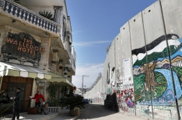 Secretive British street artist Banksy opened a hotel next to Israel's controversial separation wall in Bethlehem on Friday, his latest artwork in the Palestinian territories. / AFP PHOTO / THOMAS COEX