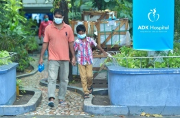 A man and child donning face masks for protection against viral fever leave ADK Hospital. PHOTO: HUSSAIN WAHEED/MIHAARU