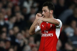 Arsenal's German midfielder Mesut Ozil celebrates after scoring the opening goal of the English Premier League football match between Arsenal and West Ham United at the Emirates Stadium in London on April 5, 2017. / AFP PHOTO / Ian KINGTON / RESTRICTED TO EDITORIAL USE. No use with unauthorized audio, video, data, fixture lists, club/league logos or 'live' services. Online in-match use limited to 75 images, no video emulation. No use in betting, games or single club/league/player publications. /