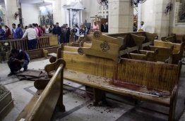 EDITORS NOTE: Graphic content / A picture taken on April 9, 2017 shows a general view of the destruction, debris, and blood stains on the benches of the Mar Girgis Coptic Orthodox Church in the Nile Delta City of Tanta, 120 kilometres (75 miles) north of Cairo, at which a bomb blast struck worshippers gathering to attend the Palm Sunday mass. / AFP PHOTO / STRINGER