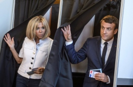 French President Emmanuel Macron (R) and his wife Brigitte Macron (L) leave the voting booth at a polling station to vote during the first round of the French legislative election in Le Touquet, on June 11, 2017. / AFP PHOTO / POOL / Christophe Petit Tesson