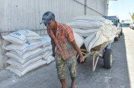 A man pulls a cart loaded with sacks of various staple food to STO's godown.