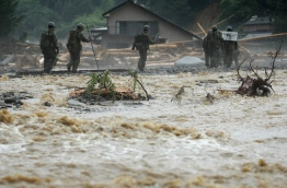 The death toll from heavy rains and flooding in southern Japan has risen to 15, a government official, as rescuers continued work to evacuate isolated survivors. / AFP PHOTO / JIJI PRESS / STR / Japan OUT