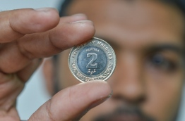 A man holds up the new, lighter MVR 2 coin. PHOTO: HUSSAIN WAHEED/MIHAARU