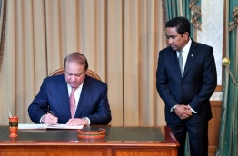 Pakistani PM Nawaz Sharif (L) signs guest book at the President's Office while President Abdulla Yameen looks on, PHOTO/PRESIDENT'S OFFICE