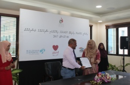 Fenaka's MD Ahmed Shareef and HRCM's President Aminath Eenas show the resolution to protect and ensure human rights.