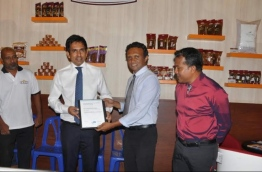 Economic Minister Mohamed Saeed (L) hands over the ISO 14001:2015 certification to Ensis Fisheries' Director Abdul Wahid at the FHAM 2017. PHOTO/ENSIS