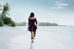 Girl in traditional dress walking along the beach in Hankede, Addu atoll. IMAGE/AISHATH NAJ