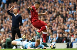 Manchester City's Spanish manager Pep Guardiola (L) gestures as Manchester City's Belgian midfielder Kevin De Bruyne (C) and Liverpool's Brazilian midfielder Roberto Firmino compete for the ball during the English Premier League football match between Manchester City and Liverpool at the Etihad Stadium in Manchester, north west England, on September 9, 2017. / AFP PHOTO / Paul ELLIS / RESTRICTED TO EDITORIAL USE. No use with unauthorized audio, video, data, fixture lists, club/league logos or 'live' services. Online in-match use limited to 75 images, no video emulation. No use in betting, games or single club/league/player publications. /