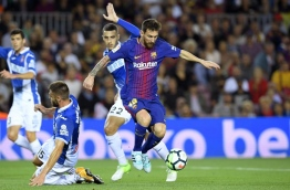Barcelona's Argentinian forward Lionel Messi (C) vies for the ball with Espanyol's midfielder David Lopez (down) and Espanyol's defender Mario Hermoso during the Spanish Liga football match Barcelona vs Espanyol at the Camp Nou stadium in Barcelona on September 9, 2017. / AFP PHOTO / LLUIS GENE