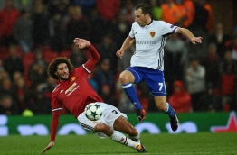 Manchester United's Belgian midfielder Marouane Fellaini (L) vies with Basel's Swiss midfielder Luca Zuffi during the UEFA Champions League Group A football match between Manchester United and Basel at Old Trafford in Manchester, north west England on September 12, 2017. / AFP PHOTO / Oli SCARFF
