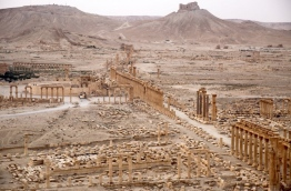 A picture taken from a helicopter during a press tour provided by the Russian Armed Forces on September 15, 2017 shows an aerial view of the ruins of Great Colonnade of the ancient city of Palmyra, in Syria's central province of Homs, with the Fakhr-al-Din al-Ma'ani Castle, known as Palmyra citadel, appearing in the background. / AFP PHOTO / France2 / Dominique DERDA