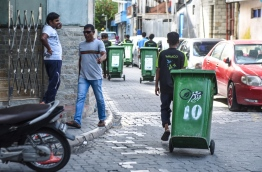 A waste collector from Waste Management Corporation (WAMCO) taking trash out of a house in the capital Male. PHOTO / MIHAARU