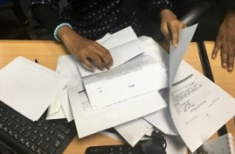 A housing ministry worker handles complaints submitted by the public regarding flat distribution of the government's first social housing project. PHOTO: NISHAN ALI/MIHAARU