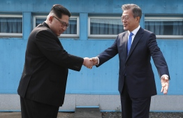 North Korea's leader Kim Jong Un (L) shakes hands with South Korea's President Moon Jae-in (R) at the Military Demarcation Line that divides their countries ahead of their summit at the truce village of Panmunjom on April 27, 2018. North Korean leader Kim Jong Un and the South's President Moon Jae-in sat down to a historic summit on April 27 after shaking hands over the Military Demarcation Line that divides their countries in a gesture laden with symbolism. / AFP PHOTO / Korea Summit Press Pool / Korea Summit Press Pool
