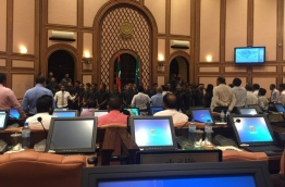 Security officers surround Speaker Maseeh inside the parliament chambers while opposition lawmakers protest.